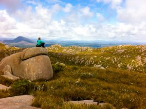A lady sits on a rock overlooking western Tasmanian wilderness