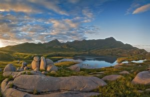 A granite range with a lake in the foreground is part of our West coat Tasmanian walking tour